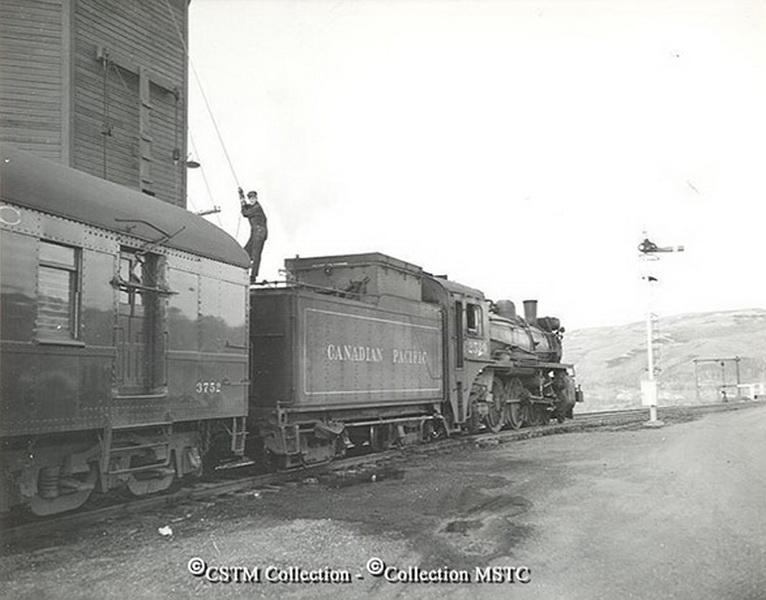 Le breakman se prépare à remplir le réservoir d'eau de la locomotive.